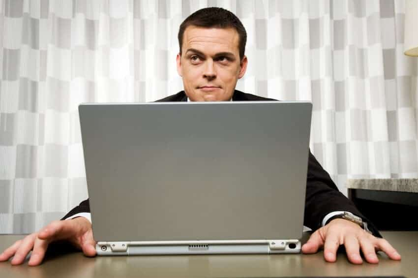 man thinking in front of laptop