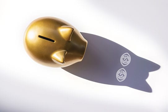 Top view gold piggy bank on white background with shadows in the eyes is money icon