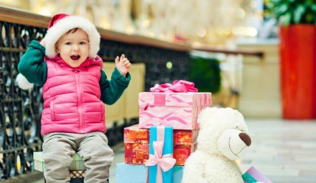 child excited next to stack of gifts