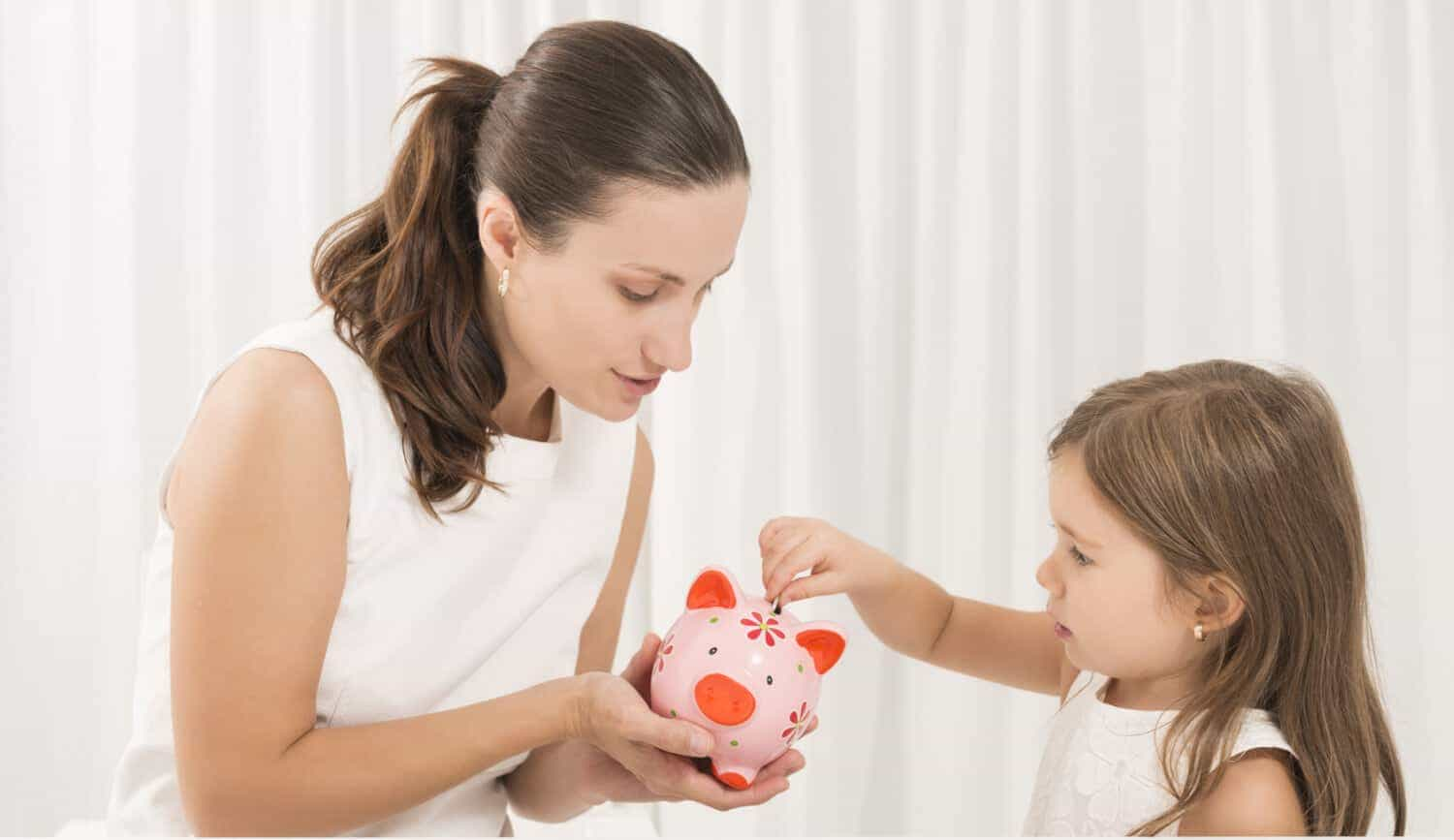 Mother helps daughter learn how to save by teaching her to put money away in a piggy bank, an crucial money lesson for kids