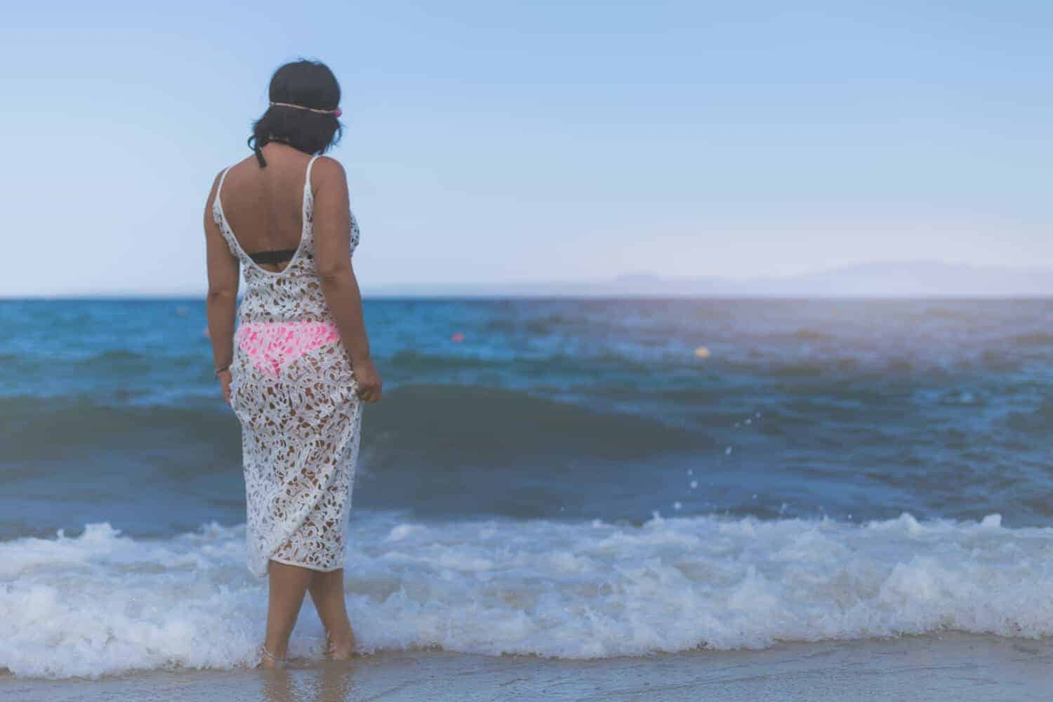 female on a beach in a white dress , casual smart , elegant clothing , splashed by water waves