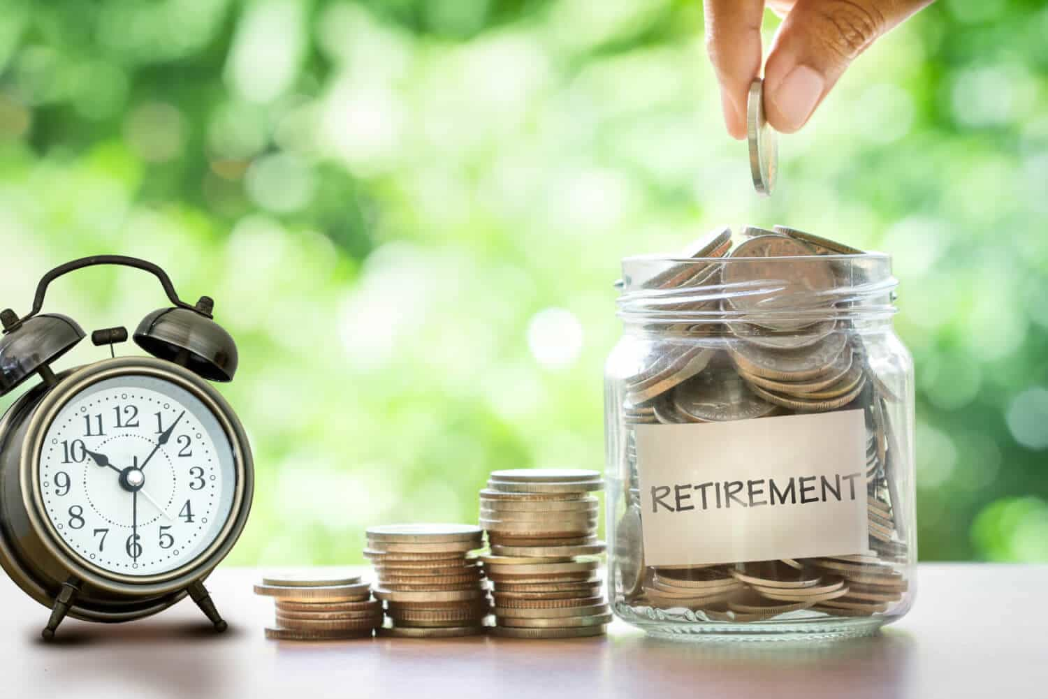 Time to think about retirement savings: Stacks of coins lead up to a retirement savings jar with an alarm clock