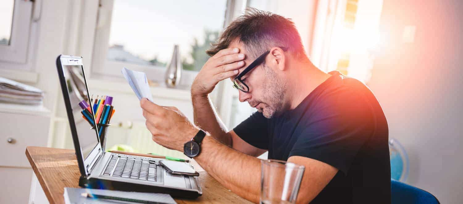 An older Gen X man sits in front of a laptop looking a bill for a debt he owes, showing signs of financial stress
