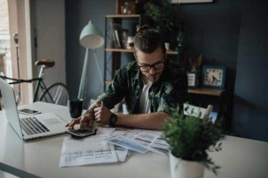 A young hipster man sits at his apartment kitchen table, pouring over his budget and finances with calculator in hand