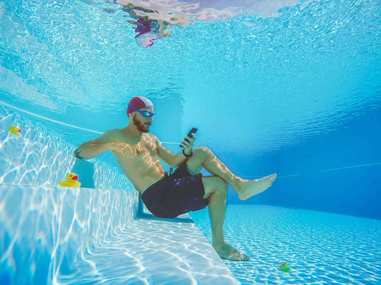 Image of man underwater using his cell phone while on vacation, oblivious to wi-fi security threats
