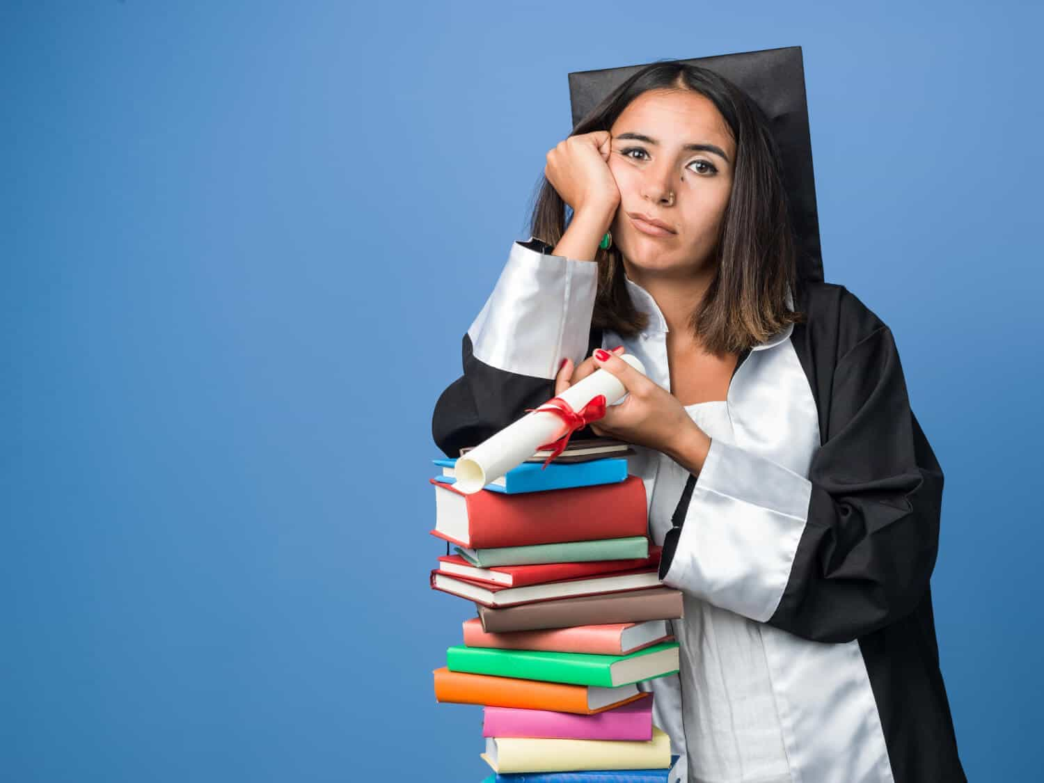 An upset college graduate rests her head on her hand after she hears recent student debt statistics
