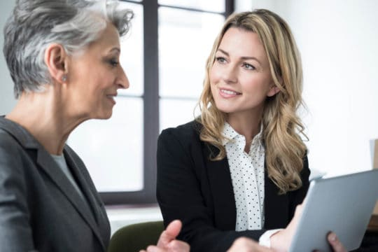older businesswoman mentoring middle aged woman about retirement planning