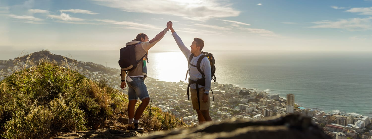 an LGBTQ couple hiking gives each other a high five