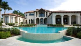 A mansion with a pool in a rich neighborhood
