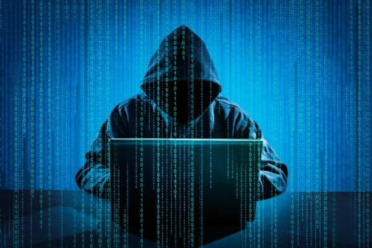 Hacker in a hoodie committing identity theft very stereotypically