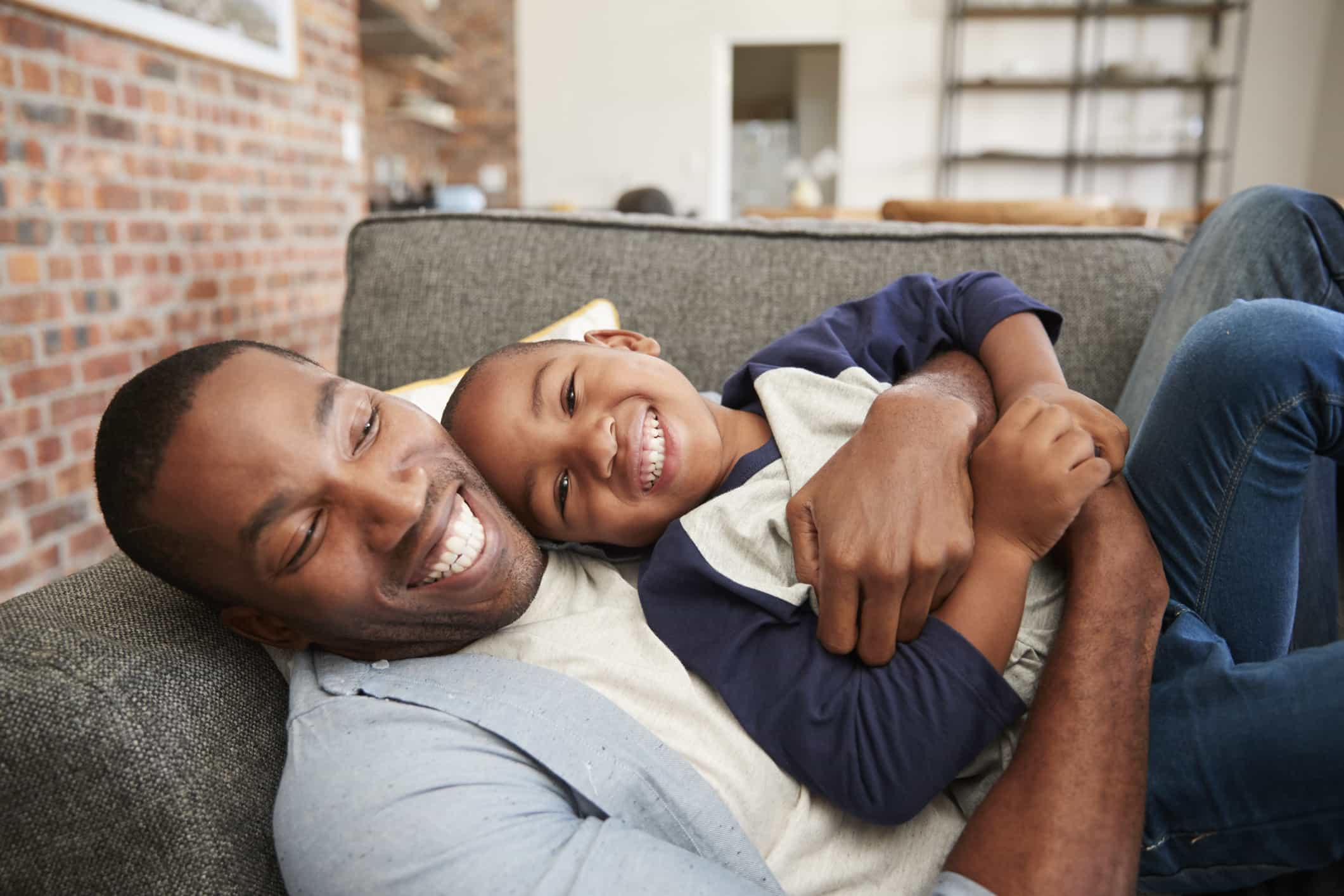 A black father and his son laugh and hug on the couch
