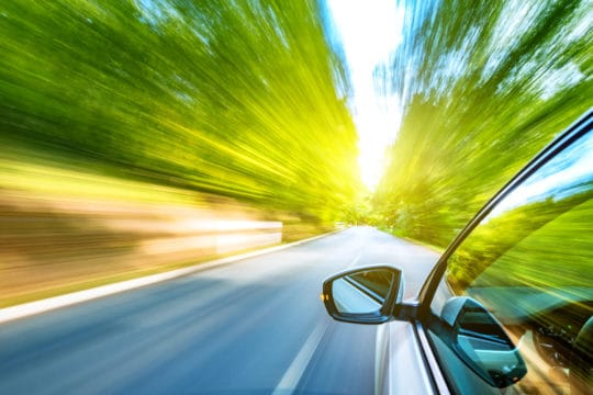 A car drives fast through a forest highway, which could affect the driver's auto insurance