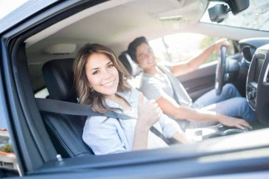 Happy couple in a car that saved on auto insurance by bundling it