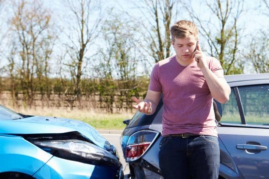 Guy calling his car insurance company after a car accident