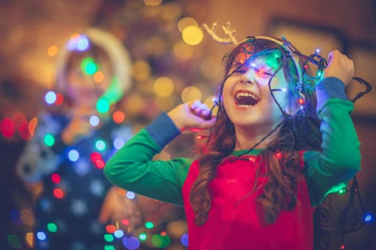 Child tangled up in Christmas lights for the holiday roundup