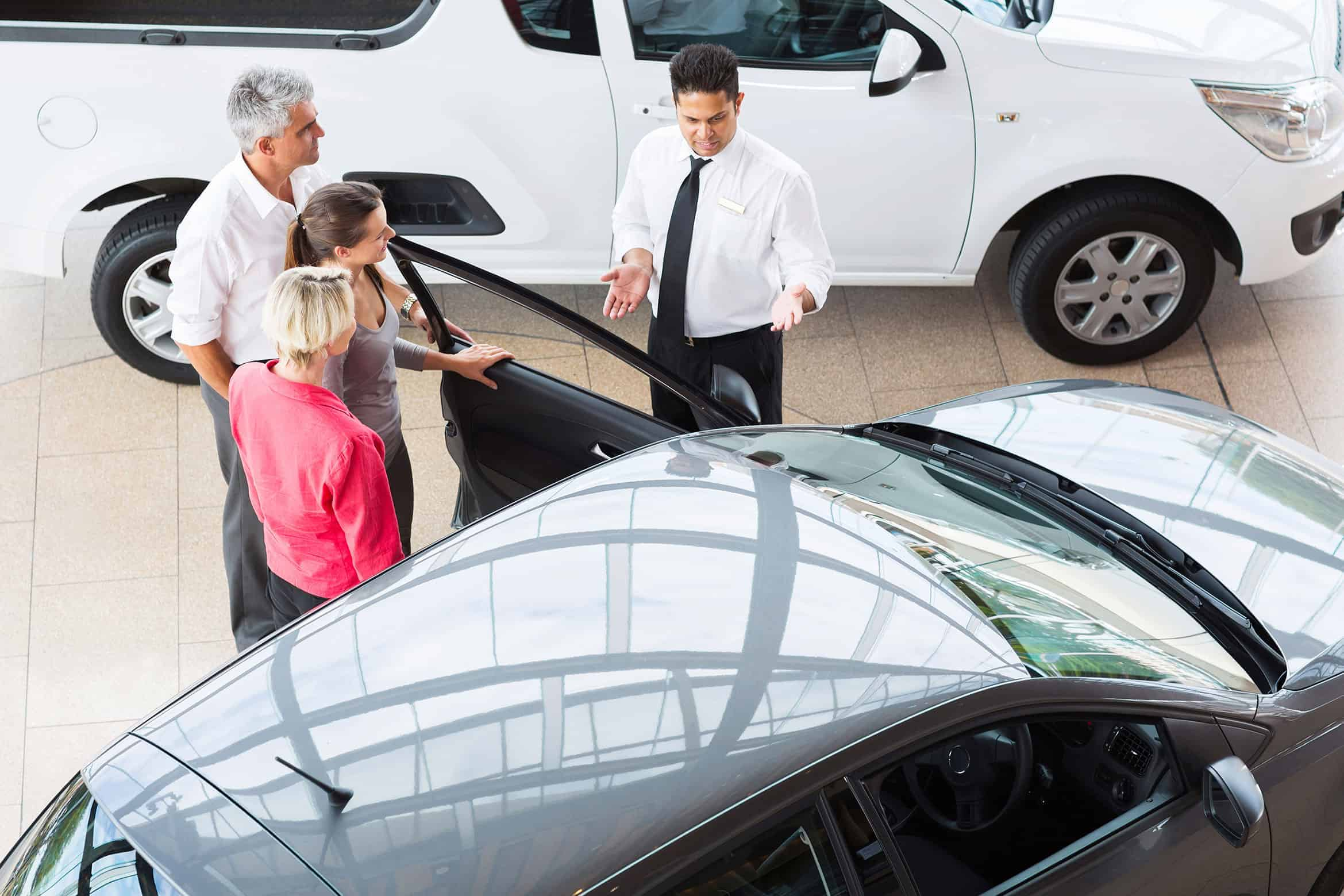 Mother, father and daughter speak with car salesman about purchasing new vehicle.