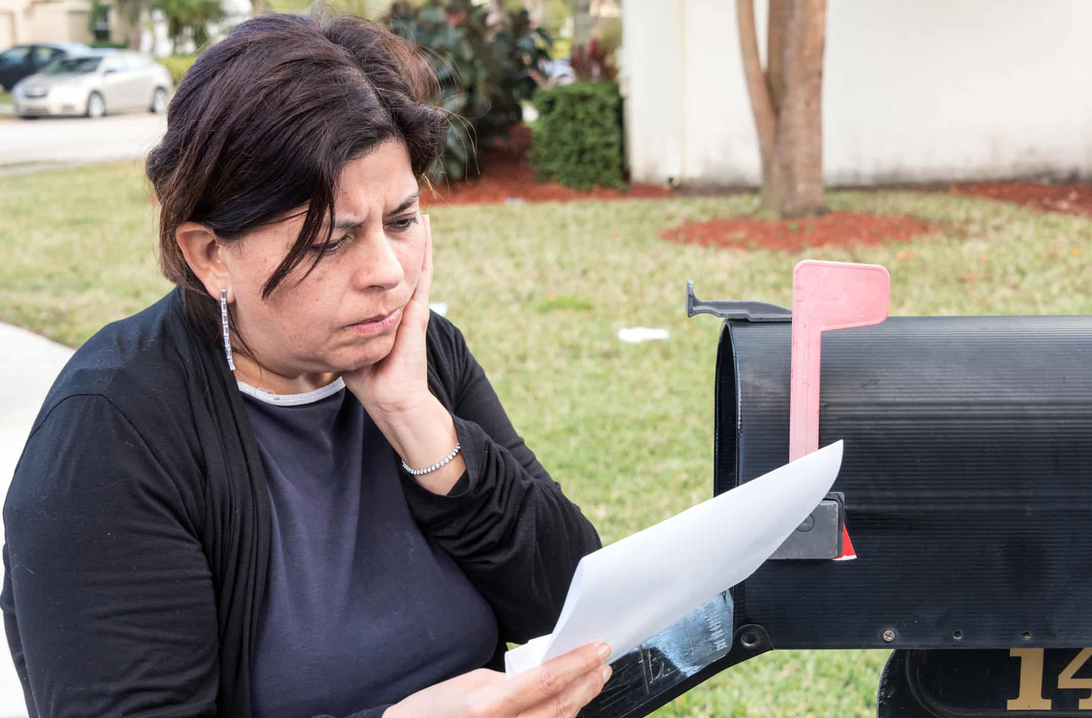 Hispanic woman reading a letter about debt settlement in her mailbox