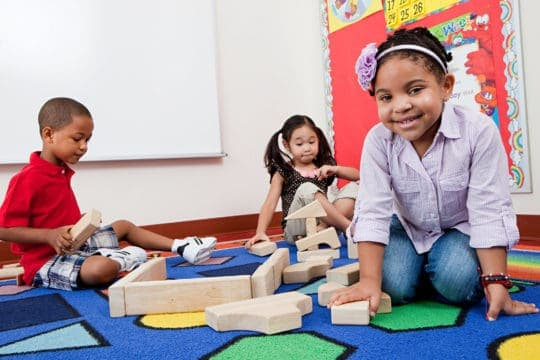 Three young children playing with building blocks in a public elementary school.