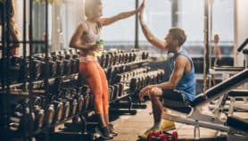 Excited couple at the gym celebrates savings on gym membership before workout