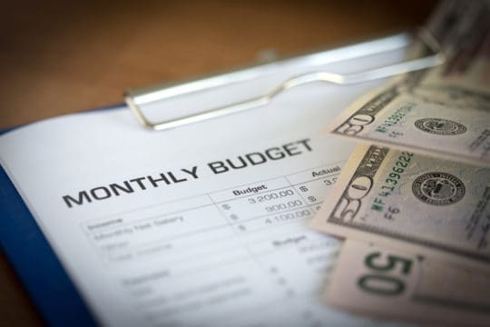 Monthly Budget on document with money laid on top.