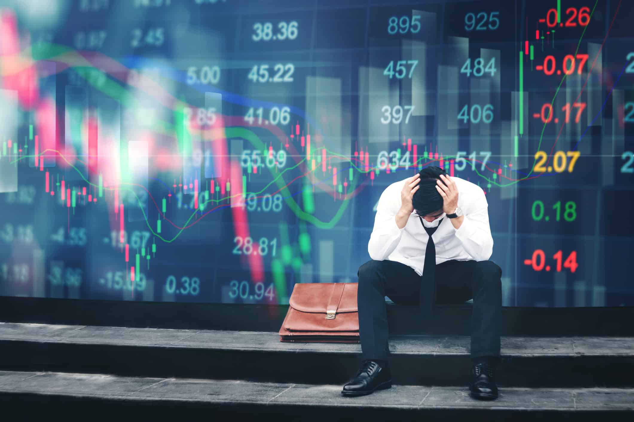 Stressed businessman sitting on the walkway in panic digital stock market financial background.