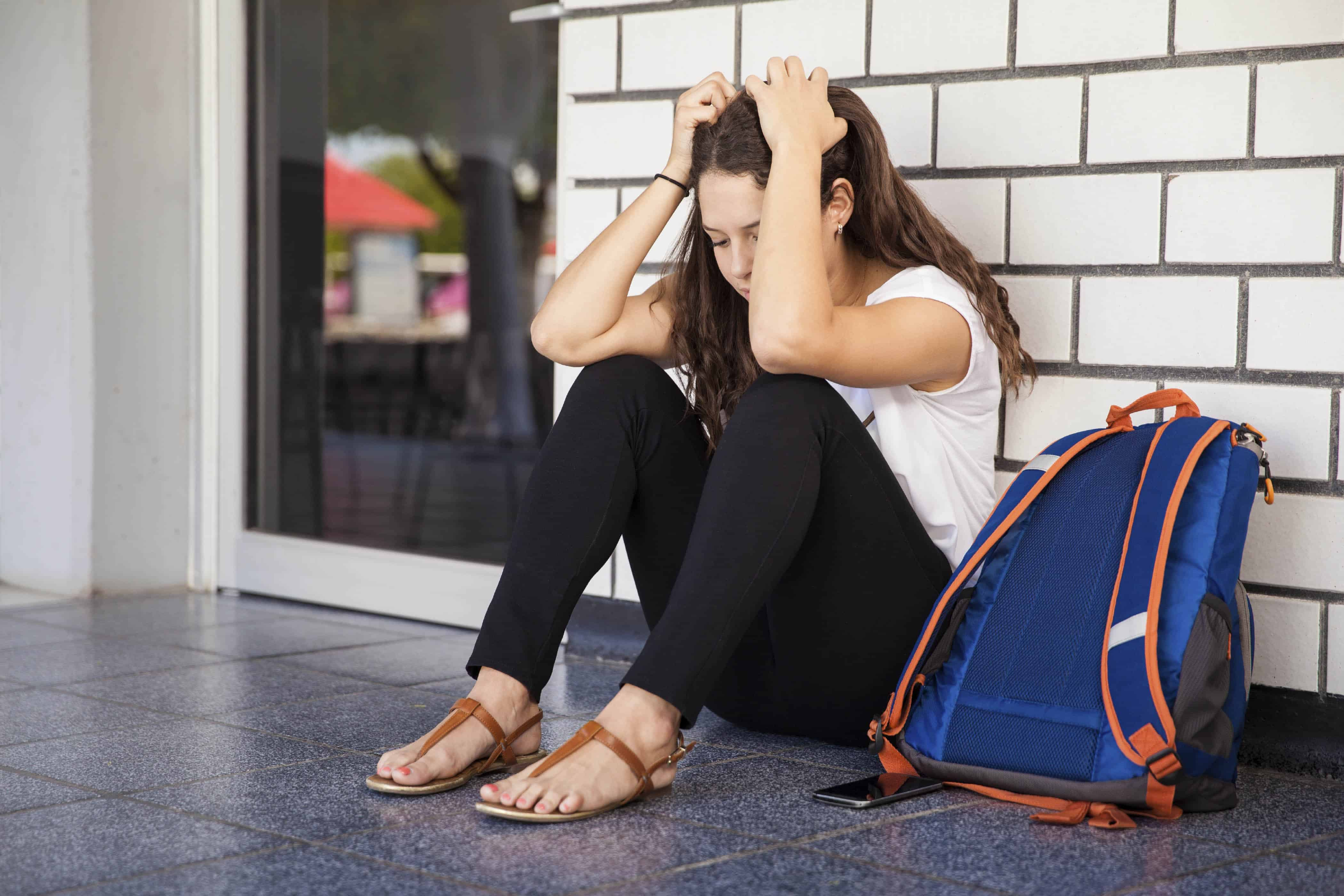 College student sitting in the hallway and feeling overwhelmed and stressed because of school
