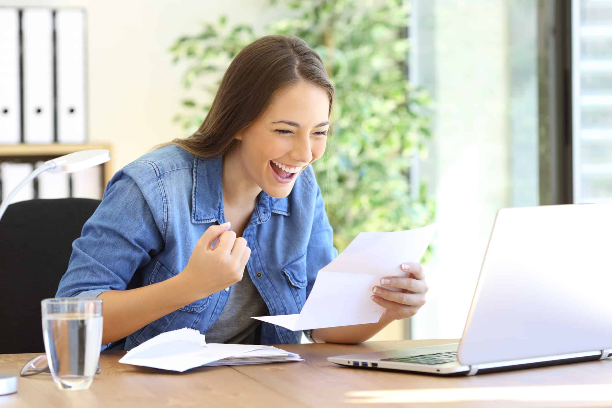 Excited woman reading good news in a letter in a desktop at office