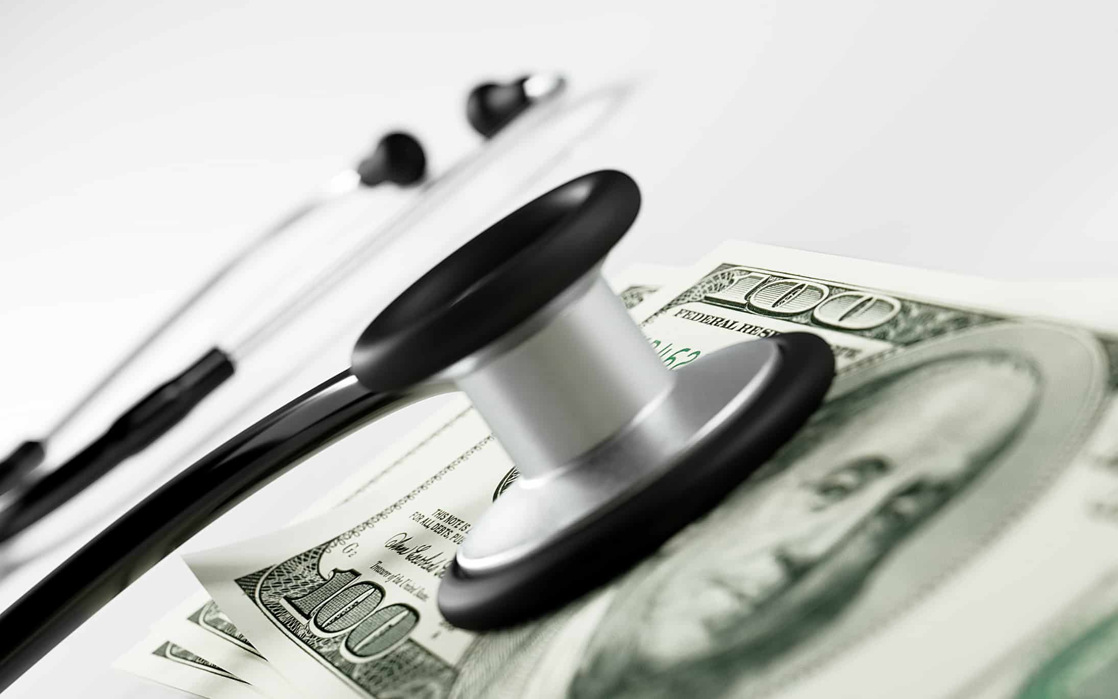 A stethoscope listens to money signifying attention to healthcare costs