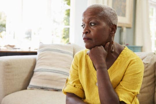 Senior black woman worries about retirement on her sofa