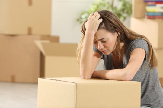 A sad woman packing up her condo because she may be forced to move out