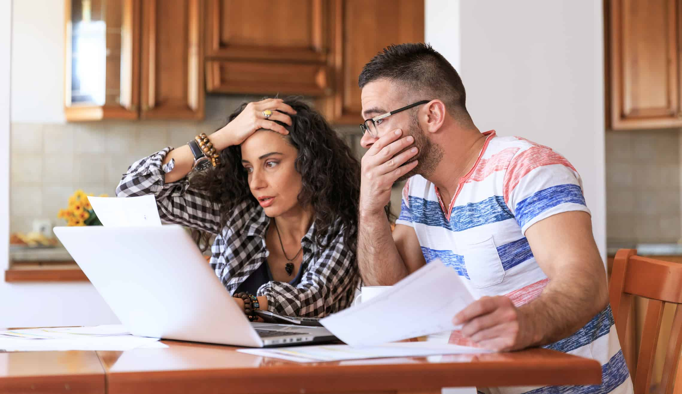 Young couple sitting at home reviewing bills.