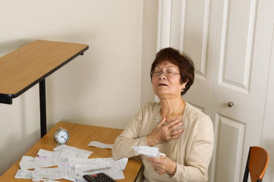 Senior woman feeling ill with her financial bills.