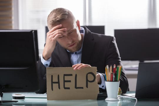 "Stressed young businessman holding cardboard with ""help"" text in office."