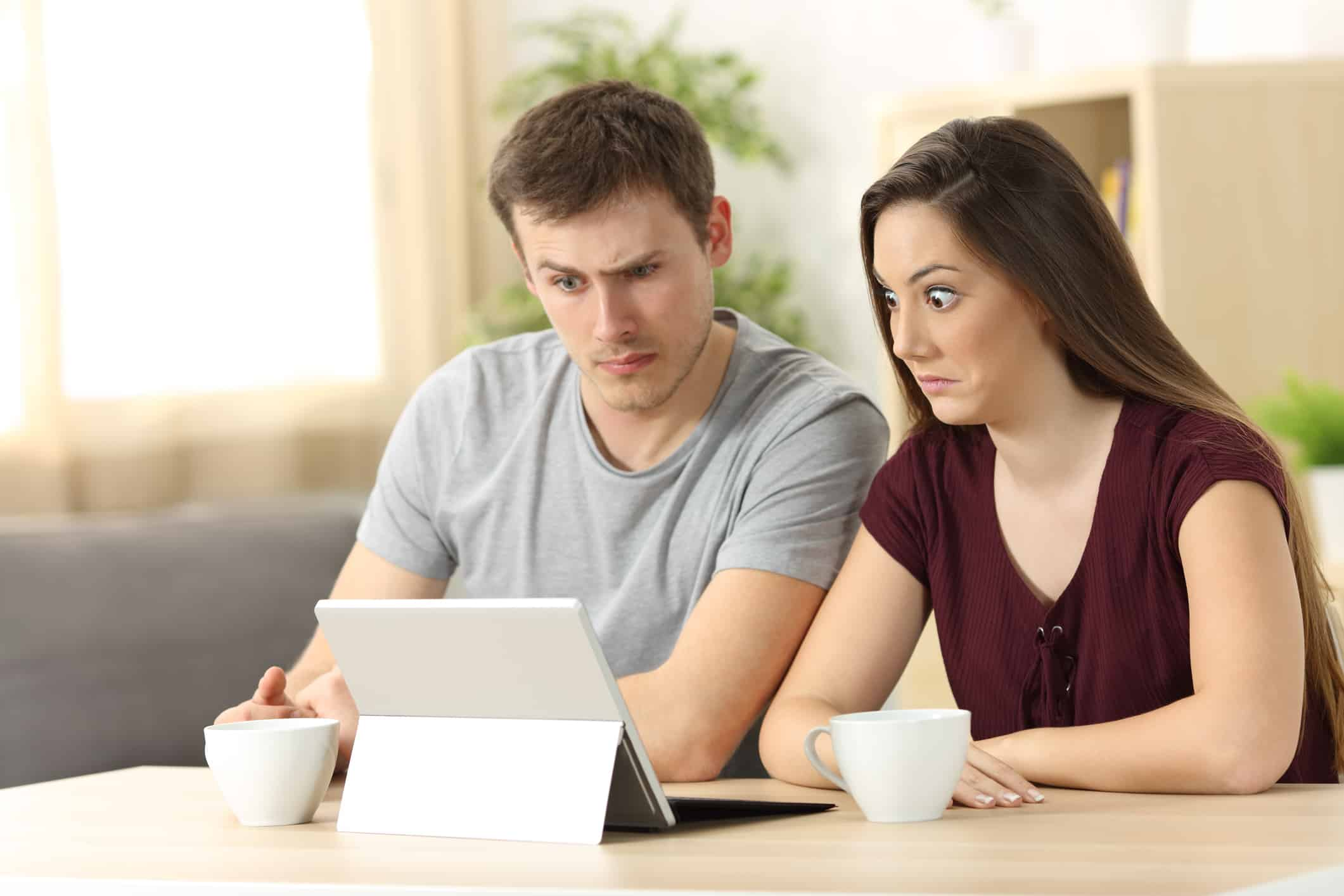 Couple looking at confusing financial information online