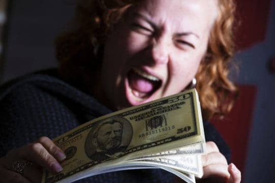 Joyful woman with wad of 50 Dollar bills