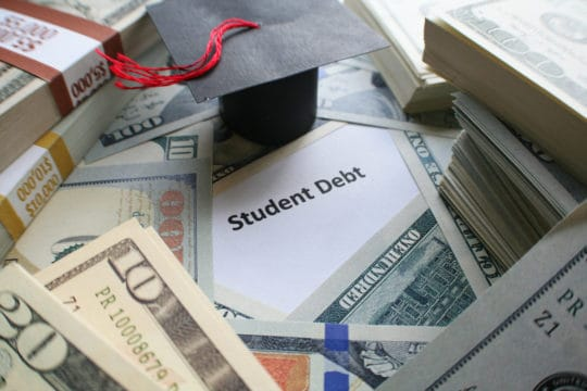 "Graduation cap and cash sit on top paper reading ""student debt"""