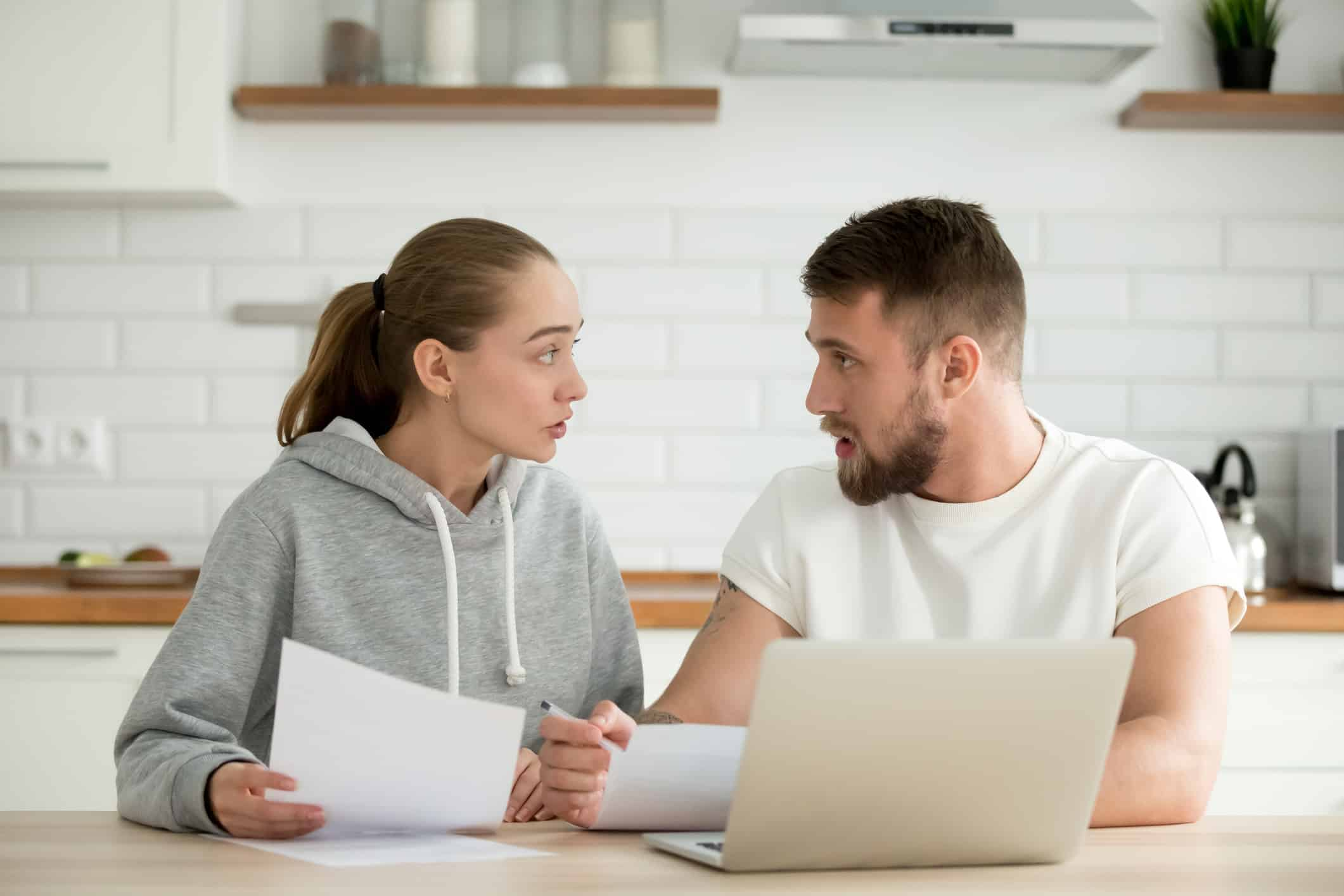 Young unhappy couple arguing about money bills documents at home kitchen.