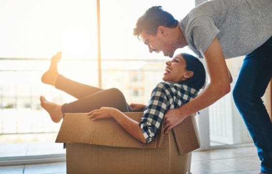 Man and woman play in a box after learning how to qualify to buy a home