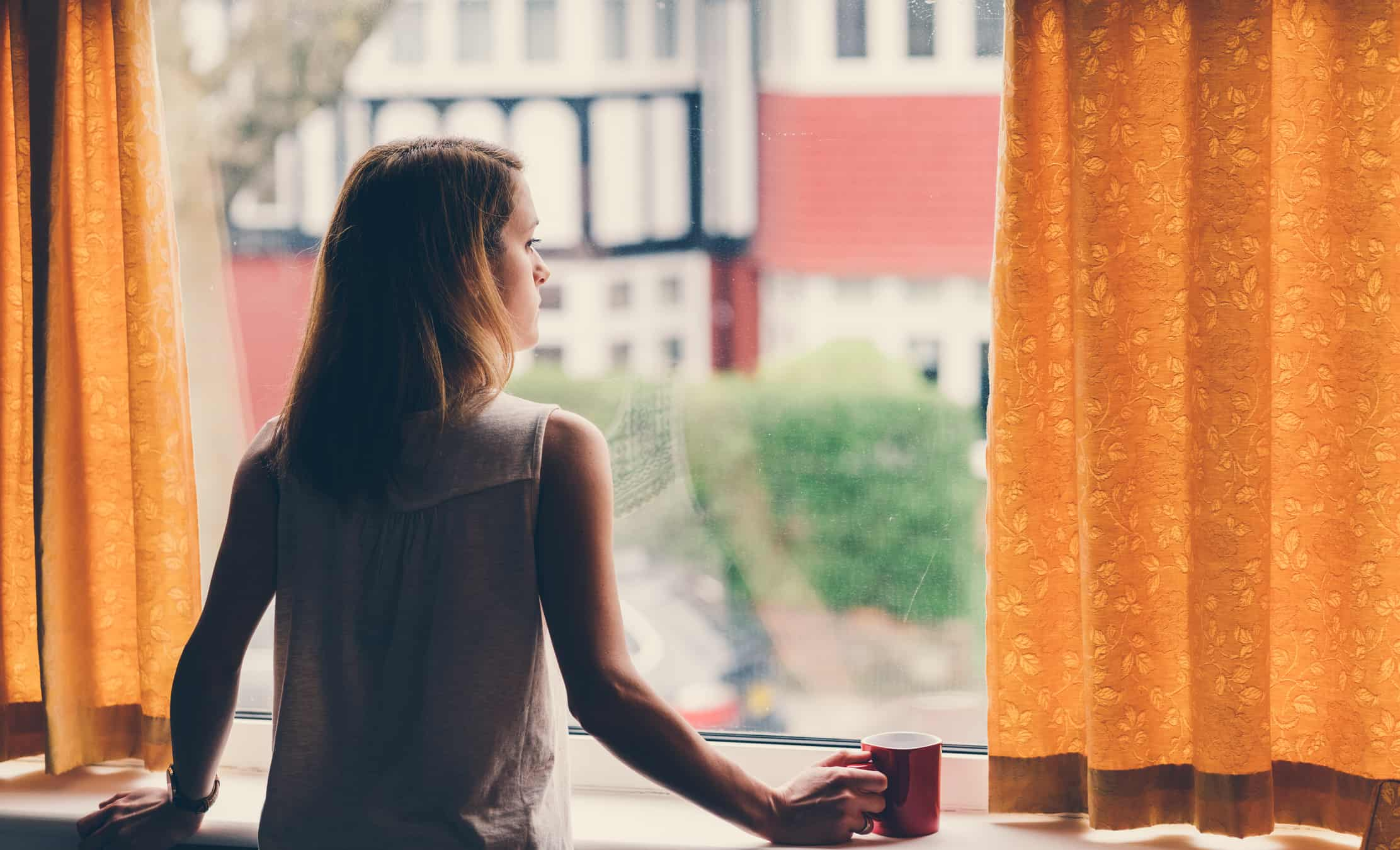 A sad, lonely woman worried about finances looks out a window with coffee