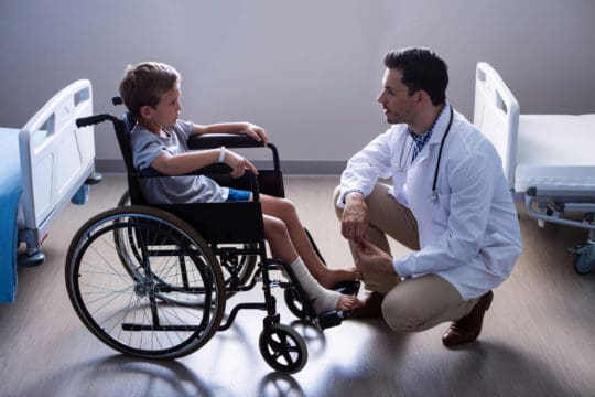 Broke Male doctor interacting with broke child patient in ward at hospital