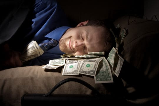 A businessman loves his money so he sleeps with it on the couch.