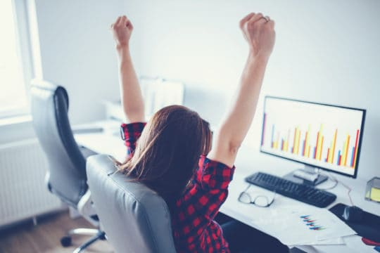 Portrait of happy young successful businesswoman celebrate something with arms up.
