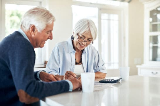 Senior couple working out their finances together at home
