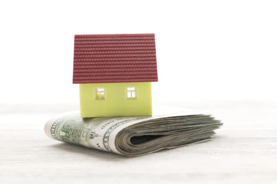 Pile of money and house on white wooden table made possible with good credit