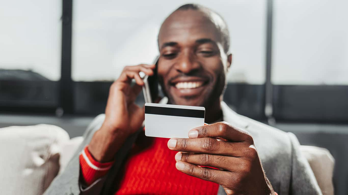 Smiling man holding credit card in one hand and cell phone up to ear in the other