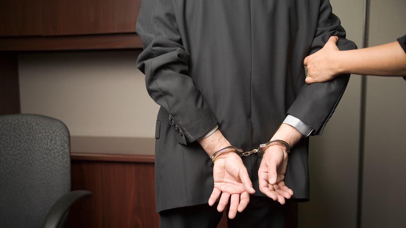 Businessman place in handcuffs
