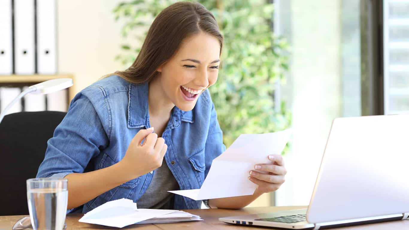 Excited entrepreneur woman reading good news in a letter in a desktop at office