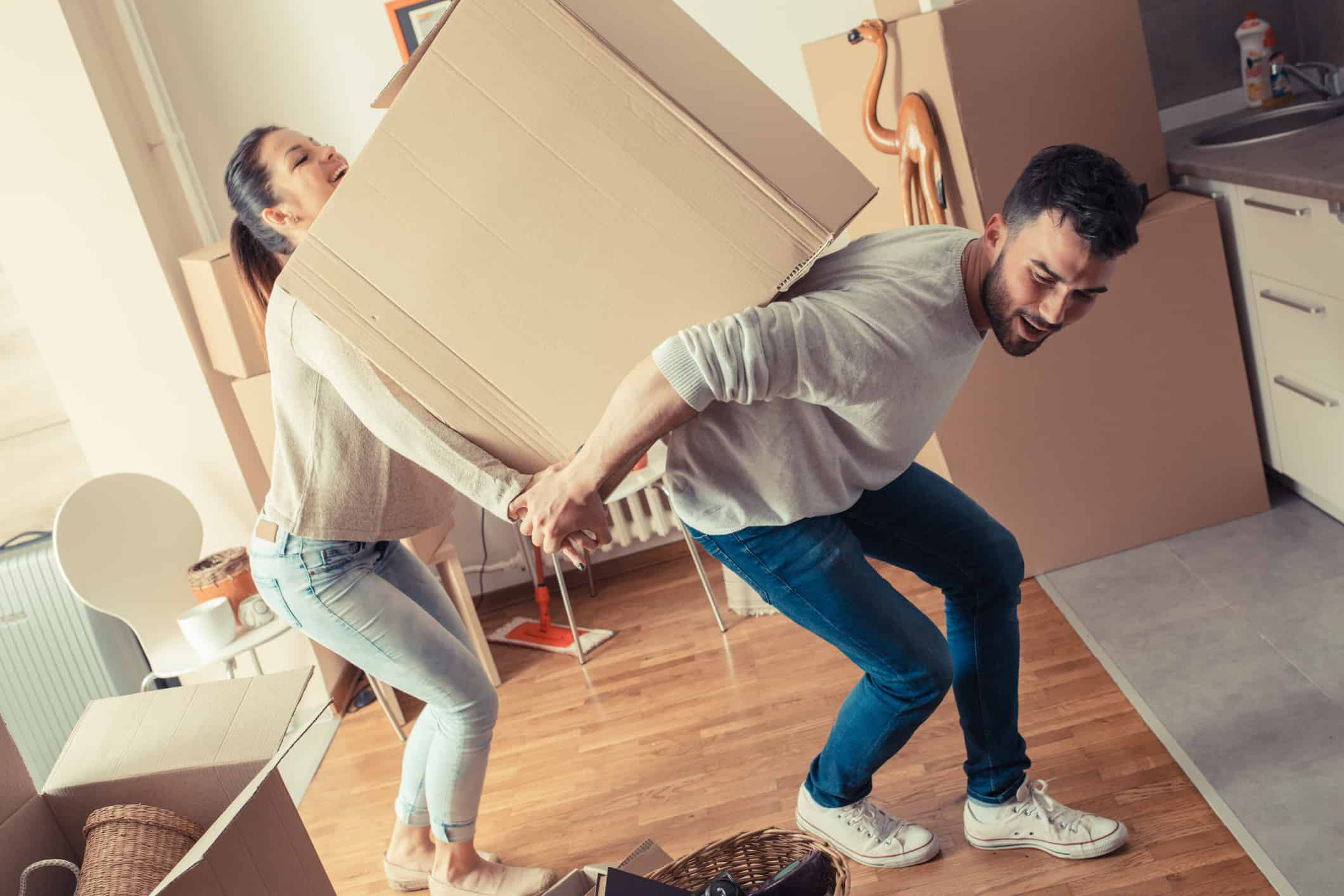 Young couple carrying big cardboard box at new home.