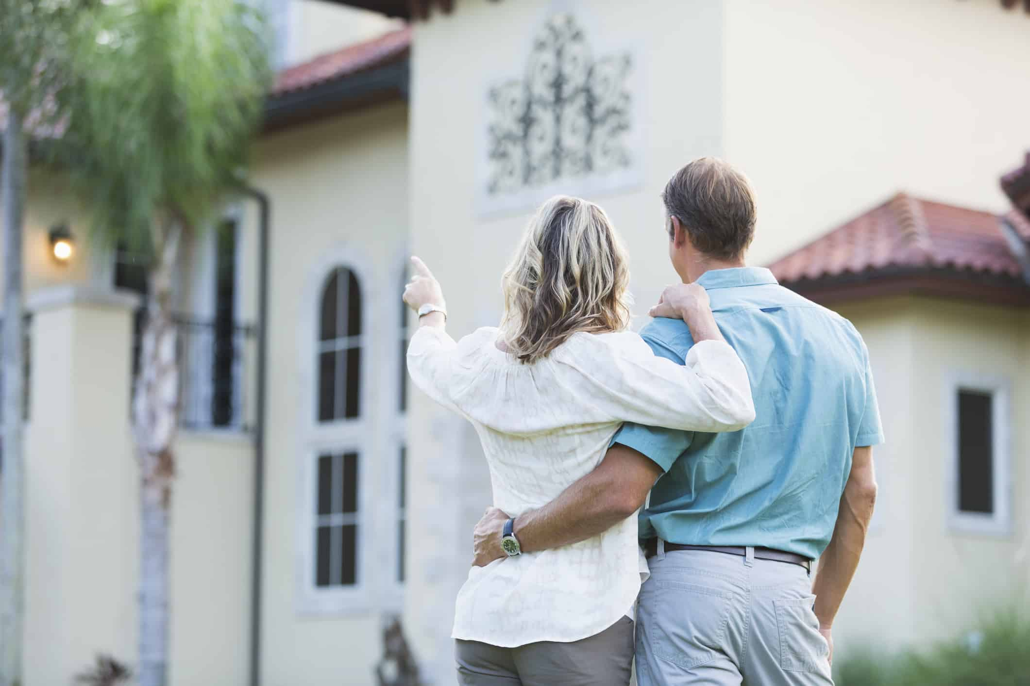 Couple looking at buying expensive homes