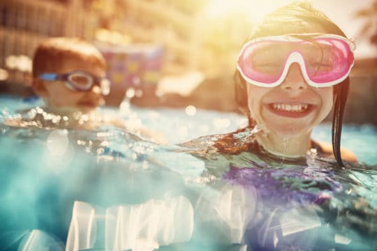 Kids swimming on family summer vacation